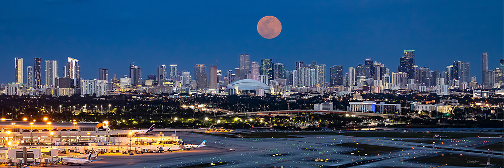 April 26, 2021: The Super Pink Moon rises over the Miami skyline as seen from the Miami International Airport Control Tower in Miami, FL.