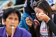 """15 JANUARY 2014 - BANGKOK, THAILAND: An anti-government protestor puts on her makeup at Shutdown Bangkok. Tens of thousands of Thai anti-government protestors continued to block the streets of Bangkok Wednesday to shut down the Thai capitol. The protest, """"Shutdown Bangkok,"""" is expected to last at least a week. Shutdown Bangkok is organized by People's Democratic Reform Committee (PRDC). It's a continuation of protests that started in early November. There have been shootings almost every night at different protests sites around Bangkok. The malls in Bangkok are still open but many other businesses are closed and mass transit is swamped with both protestors and people who had to use mass transit because the roads were blocked.    PHOTO BY JACK KURTZ"""
