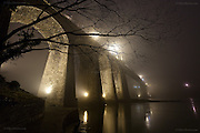 Night time fog swirls in from the Irish Sea and up the Menai Strait, enveloping the Menai Suspension Bridge (Welsh: Pont Grog y Borth) which is a stone built Victorian suspension bridge between the island of Anglesey and Bangor and mainland of Wales. The 100ft high bridge was designed by Thomas Telford and completed in 1826.