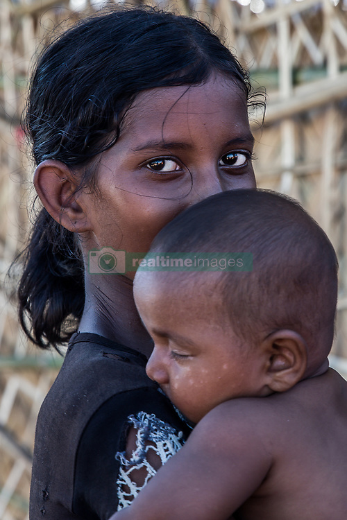 February 6, 2018 - Cox'S Bazar, Bangladesh - A young Rohingya girl and baby seen posing for a photo in Kutupalong refugee camp in Cox's Bazar. More than 800,000 Rohingya refugees have fled from Myanmar Rakhine state since August 2017, as most of them keep trying to cross the border to reach Bangladesh every day. (Credit Image: © Marcus Valance/SOPA via ZUMA Wire)