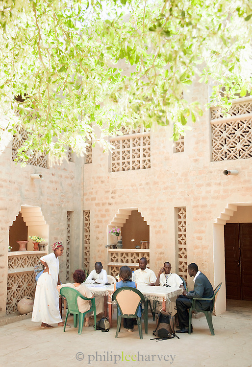 Toursits and locals sit at a table in a hotel courtyard in Djenné, Mali