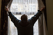 Rob opening his curtains. He was recently living on the streets of Peterborough.  With the help of Hope into Action he is now settled into safe and secure housing and is building connections with his family. Peterborough, Cambridgeshire. UK