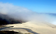 A heavy blanket of fog rolls from the ocean across a beach and up a mountainside in Big Sur, California