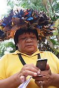 Chief Almir Narayamogo Surui in his office in Cacaol<br /> <br /> An Amazonian tribal chief Almir Narayamogo, leader of 1350 Surui Indians in Rondônia, near Cacaol, Brazil, with a $100,000 bounty on his head, is fighting for the survival of his people and their forest, and using the world's modern hi-tech tools; computers, smartphones, Google Earth and digital forestry surveillance. So far their fight has been very effective, leading to a most promising and novel result. In 2013, Almir Narayamogo, led his people to be the first and unique indigenous tribe in the world to manage their own REDD+ carbon project and sell carbon credits to the industrial world. By marketing the CO2 capacity of 250 000 hectares of their virgin forest, the forty year old Surui, has ensured the preservation, as well as a future of his community. <br /> <br /> In 2009, the four clans and 25 Surui villages voted in favour of a total moratorium on logging and the carbon credits project. <br /> <br /> They still face deforestation problems, such as illegal logging, and gold mining which causes pollution of their river systems