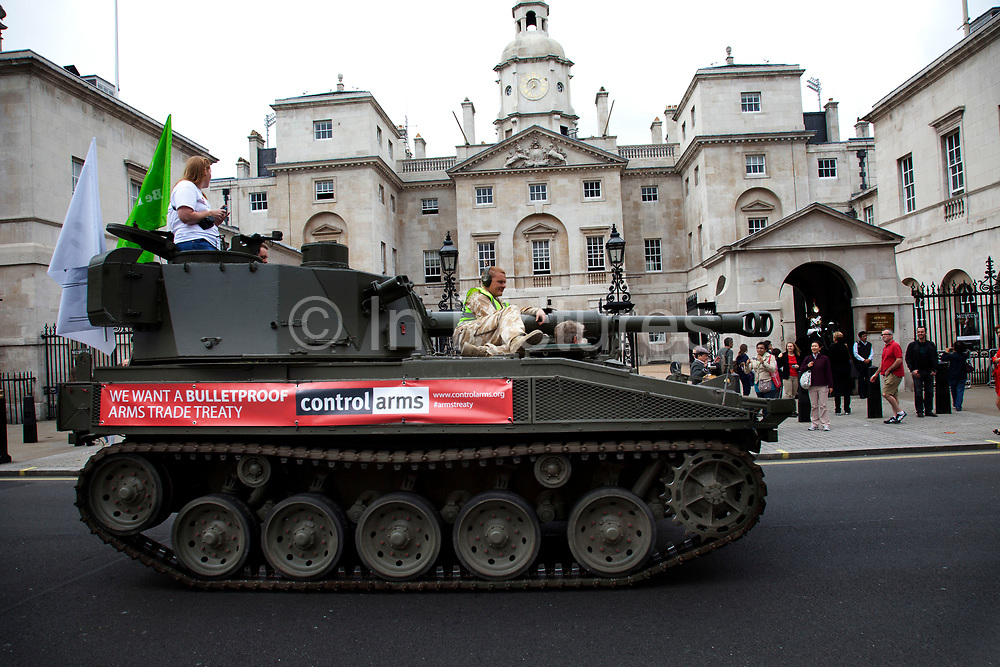 Tank passes Horse Gurads Parade on Whitehall. Campaigners and supporters from Oxfam and Amnesty International, as part of the Control Arms coalition, drive an Abbot gun tank around central London to highlight the need for a global Arms Trade Treaty (ATT) to be agreed during a United Nations conference next month (July 2012). London, England, UK. 27th June 2012.