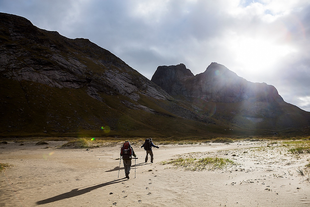Liana (left) and Parmenter Welty hike into the sun above Horseid Beach, Moskenesoya, Lofoten Islands, Norway.