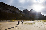 Liana (left) and Parmenter Welty hike into the sun above Horseid Beach, Moskenesoya, Lofoten Islands, Norway.