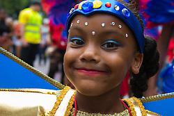 London, August 30th 2015. A little girl grins for the camera as revellers enjoy Family Day at the Notting Hill Carnival.