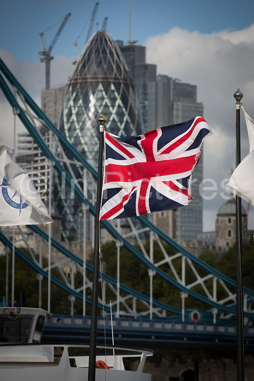 The Union Jack flag flies in the foreground of Tower Bridge and construction work in progress next to the Swiss Re Building aka the Gherkin in the capitals financial district The Square Mile behind, on 5th October, 2017, in London, England.