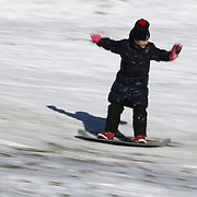 A young girl snowboarding in Central Park after New York City was hit with over 7 inches of snow during its first winter storm of the year. Central Park, Manhattan, New York, USA. 4th January 2014 Photo Tim Clayton