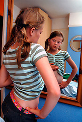 Girl looking at her tummy in a mirror