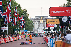 London, UK. 3 August, 2019. Race officials tend to an injured rider towards the end of the Brompton World Championship Final. More than 500 smartly-dressed Brompton riders compete in the race over a 16km 8-lap circuit around St James's Park following a Le Mans-style dash at the start. It was the fifth successive year that the race had featured as part of the Prudential RideLondon event.