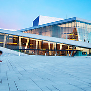 The Oslo Opera House (Operhuset) in Olso, Norway, at sunset. Designed by the Norwegian firm Snøhetta, the building was completed in 2007 and is the home of the Norwegian National Opera and Ballet, and the national opera theatre in Norway. It is situated in the Bjørvika neighborhood of central Oslo, at the head of the Oslofjord.<br />