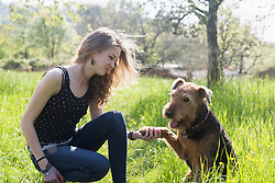 Teenage girl sitting in park with her dog, Freiburg im Breisgau, Baden-Wuerttemberg, Germany