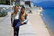 Two boys friends with arms around each other on wall above sandy beach, Calvi, Corsica, France, 1950s