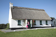 Mother and daughter stand at door of thatched holiday home house, Ballyvaughan, County Clare, Ireland