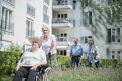 Senior man and women with mobility walker and wheelchair at garden, Bavaria, Germany, Europe
