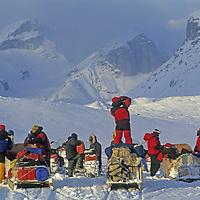 BAFFIN ISLAND, Nunavut, Canada. Expedition snowmobiles into Stewart Valley, a setting of huge polar cliffs.