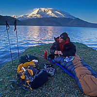 Mark Newcomb (MR) wakes from a bivouac by Lake Karakul in the Pamir Mountains of Xinjiang province in far western China.  Behind him is [Mount] Mustagh Ata.