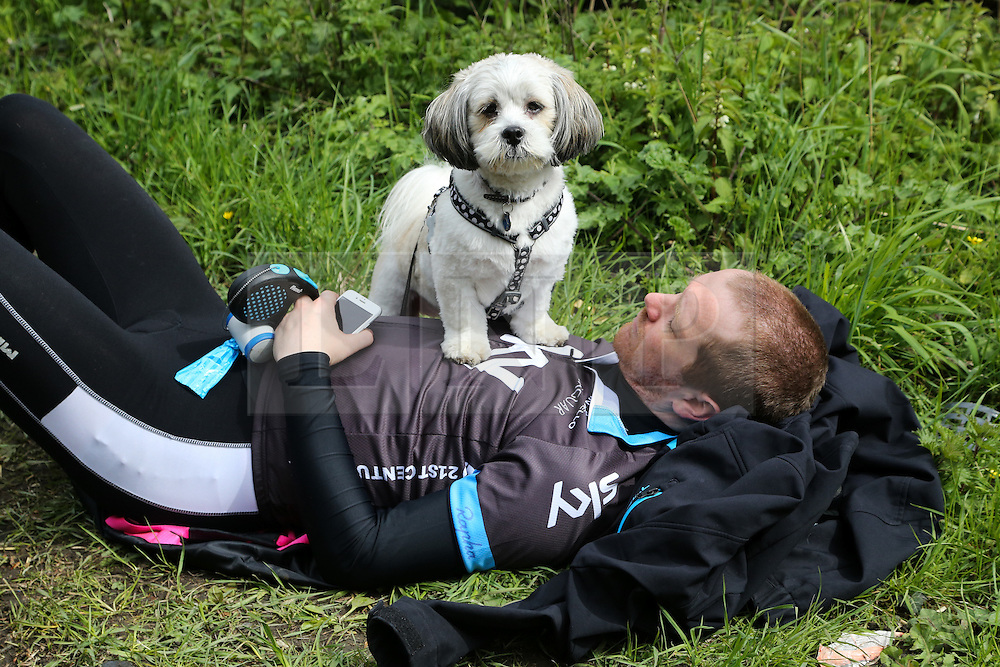 © Licensed to London News Pictures. 30/04/2016. Harewood, UK. A spectator lays with his dog on him as he waits for the riders to ascend the climb in Harewood near Leeds in West Yorkshire during the second stage of the 2016 Tour De Yorkshire. The three-day road cycling race held annually across Yorkshire is in it's second year. Photo credit : Ian Hinchliffe/LNP