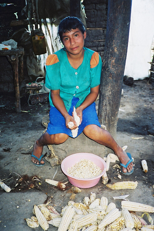 A young Maya Chortí woman degrains maize in her kitchen in the Copán region of Honduras