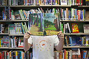 A man holds a copy of the children's book, The Gruffalo in front his face. He is standing in front of a bookshelf full of books. HMP Kingston, Portsmouth, United Kingdom. As part of the Storybook Dads Program a prisoner reads a story for his 6-year-old daughter. HMP Kingston.