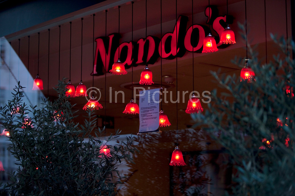 Window of Nando's lit up with red lamps. Nando's is a casual dining restaurant group originating from South Africa with a Portuguese/Mozambican theme. Founded in 1987, Nando's operates in 30 countries on 5 continents.