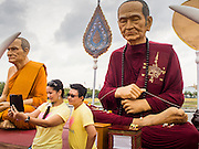 "08 JANUARY 2015 - BANGKOK, THAILAND: Women take ""selfies"" of each other in front of a statue of a revered Buddhist monk on Sanam Luang. Buddhist in Bangkok have a chance to meditate in front of seven large statues of revered Buddhist monks and worship a hair relic of the Buddha at a series of altars on Sanam Luang near the Grand Palace in Bangkok.    PHOTO BY JACK KURTZ"