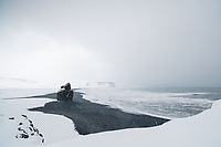 Reynisfjara black sand beach during snowfall in winter. Arnardrangur Sea Stack. South Iceland.