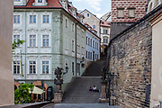 "A couple sitting on the Townhall Stairs ""Radnicke schody""close to Prague castle. ""Nerudova street"" on the left. The Czech government lowered the security measures and as of Monday 25 May 2020, wearing of protective masks will be mandatory only in the interiors of buildings other than the place of residence and in public transport."