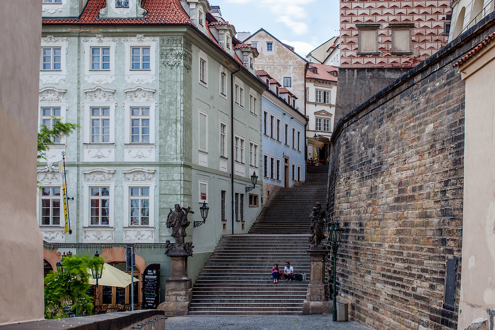 """A couple sitting on the Townhall Stairs """"Radnicke schody""""close to Prague castle. """"Nerudova street"""" on the left. The Czech government lowered the security measures and as of Monday 25 May 2020, wearing of protective masks will be mandatory only in the interiors of buildings other than the place of residence and in public transport."""