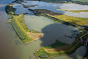 Nederland, Brabant, Gemeente Werkendam, 12-06-2009; Polder Noordwaard in de Biesbosch, onderdeel van 'Ruimte voor de Rivier' (bescherming tegen hoogwater door rivierverruiming). Door het gedeeltelijke afgraven van de dijken zijn in- en uitstroomopeningen in de Merwededijk gemaakt (links). Ten gevolge van deze maatregelen zijn landerijen (gedeeltelijk) onder water komen te staan. Bij hoge waterstanden wordt het water door het nieuw ontstane doorstroomgebied van de Nieuwe Merwede afgeleid en zo westelijk mogelijk afgevoerd, richting Hollandsch Diep (buiten beeld). De kans op overstromingen in de bovenloop van de rivier is hierdoor kleiner..Polder Noordwaard (part of Biesbosch National Park), part of the program 'Space for the River' (protection against high water by means of creating space for the rivers). Because the dike next to the river has been partly excaveted, entrances for the water of the river have been made (left). As a consequence the former polder can now store water and allows the river to flood more easily downstream (direction of the Northsea). These measures dimishes the risk of floods further upstream at high water in the winter  .Swart collectie, luchtfoto (25 procent toeslag); Swart Collection, aerial photo (additional fee required).foto Siebe Swart / photo Siebe Swart