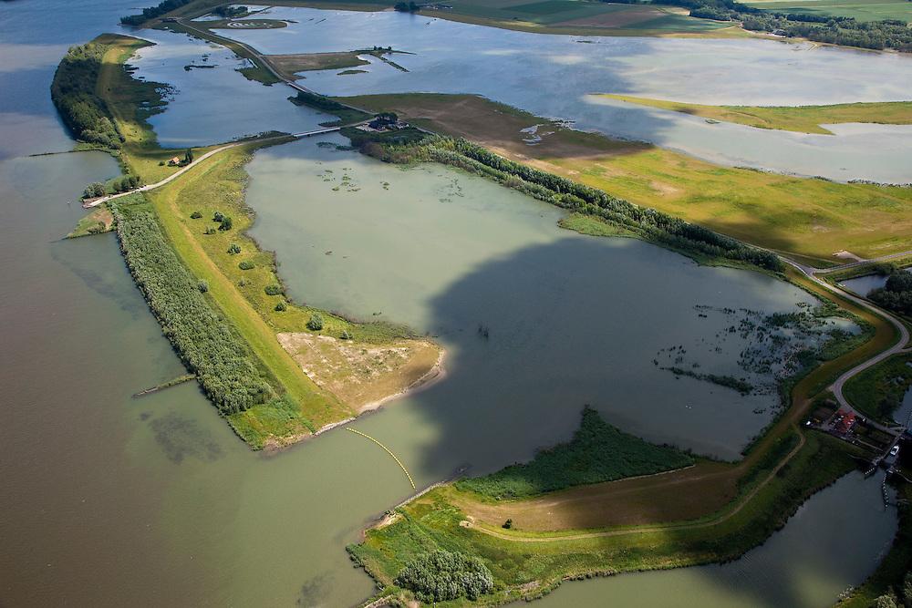 Nederland, Brabant, Gemeente Werkendam, 12-06-2009; Polder Noordwaard in de Biesbosch, onderdeel van 'Ruimte voor de Rivier' (bescherming tegen hoogwater door rivierverruiming). Door het gedeeltelijke afgraven van de dijken zijn in- en uitstroomopeningen in de Merwededijk gemaakt (links). Ten gevolge van deze maatregelen zijn landerijen (gedeeltelijk) onder water komen te staan. Bij hoge waterstanden wordt het water door het nieuw ontstane doorstroomgebied van de Nieuwe Merwede afgeleid en zo westelijk mogelijk afgevoerd, richting Hollandsch Diep (buiten beeld). De kans op overstromingen in de bovenloop van de rivier is hierdoor kleiner..Polder Noordwaard (part of Biesbosch National Park), part of the program 'Space for the River' (protection against high water by means of creating space for the rivers). Because the dike next to the river has been partly excaveted, entrances for the water of the river have been made (left). As a consequence the former polder can now store water and allows the river to flood more easily downstream (direction of the Northsea). These measures dimishes the risk of floods further upstream at high water in the winter  .Swart collectie, luchtfoto (25 procent toeslag); Swart Collection, aerial photo (additional fee required).foto Siebe Swart / photo Siebe Swart