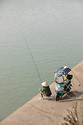 High angle view of a male fisherman in a traditional Asian style conical hat fishing in the Hengjiang River, Tunxi district, Huangshan City, Anhui Province, China