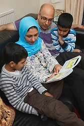 Asian family sitting on a sofa reading a children's book.