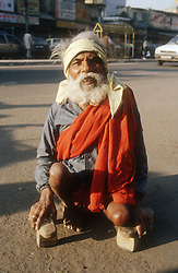 Elderly man crouching on the ground holding wooden blocks which he uses to help him walk,