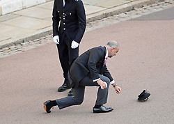 A guest loses his hat in the wind as he arrives for the wedding of Princess Eugenie to Jack Brooksbank at St George's Chapel in Windsor Castle.