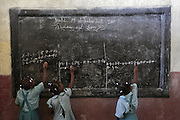 Kindergarten students write their abc's on a well work blackboard.  Various grade levels attend school at the Church of Christ school in Saint Roch mountain above Carrefour, Haiti.  The classes are conducted in a concrete building with a concrete floor.  The 6th grade is conducted in the church.