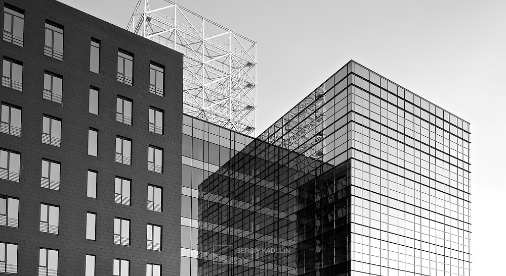 Black and white architectural shot of business centre located at Moskovsky avenue, 28 in Kyiv, Ukraine. Front of the building is covered with glass. reflecting sky and construction elements.