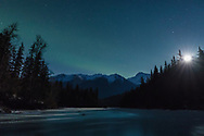 The aurora borealis and the rising moon over Mosquito Lake near Haines in Southeast Alaska. Winter. Evening.