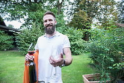 Young man with a blanket and wine glasses in garden, Bavaria, Germany