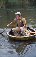 man sailing traditional hand made coracles on river