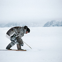 An Inuit hunter waits by a seal breathing hole north of Baffin Island.