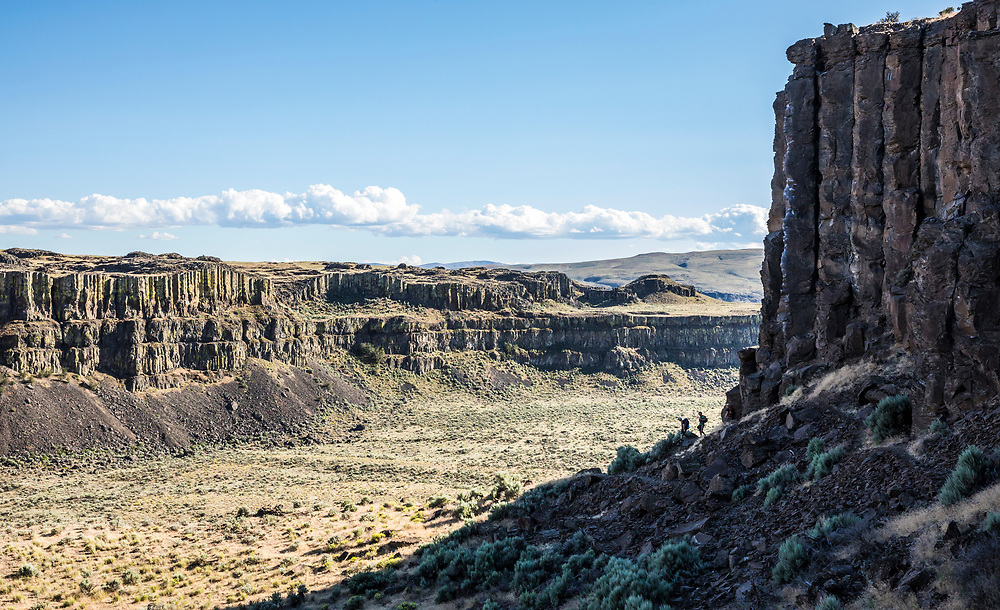 Three climbers in a rocky desert landscape. Echo Basin, Eastern Washington, USA.