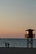 Men walking on La Caleta beach at sunset in Cadiz, Spain
