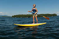 Bunny Brauns enjoys the afternoon on a stand up paddle board making her way through Lockes Island and Varney Point on Lake Winnipesaukee Thursday.(Karen Bobotas/for the Laconia Daily Sun)