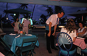 As a couple inspect the menu on the sidewalk, a waiter attends to customers at an outdoor restaurant and bar on Ocean Drive,  on 15th May 1996, in Miami Beach, Florida, USA.