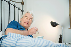 Portrait of mature man in bed with coffee cup, smiling