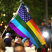 A woman holds up a rainbow flag during a vigil at the Dr. Phillips Center for the Performing Arts for the victims of a mass shooting at the Pulse nightclub Monday, June 13, 2016, in Orlando, Florida.  A gunman killed dozens of people in a massacre at the crowded gay nightclub in Orlando on Sunday, making it the deadliest mass shooting in modern U.S. history. (Alex Menendez via AP)