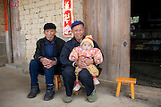 Men with a young baby in Fuli Old Town, Xingping. China has a one child policy to limit population.